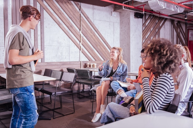 Comunicação agradável. homem bonito parado em posição de meia enquanto fala com seus colegas