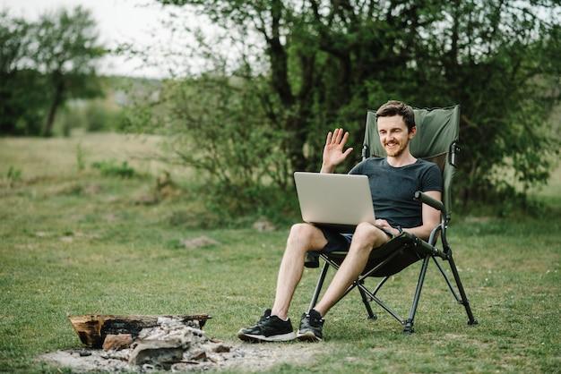 Comunicação com parentes, família online no laptop na natureza. homem instruindo a equipe na conferência ou consulta de trabalho remoto, trabalhador falar, falar em videochamada com colegas.