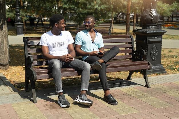 Comunicação de dois homens africanos no verão em um banco