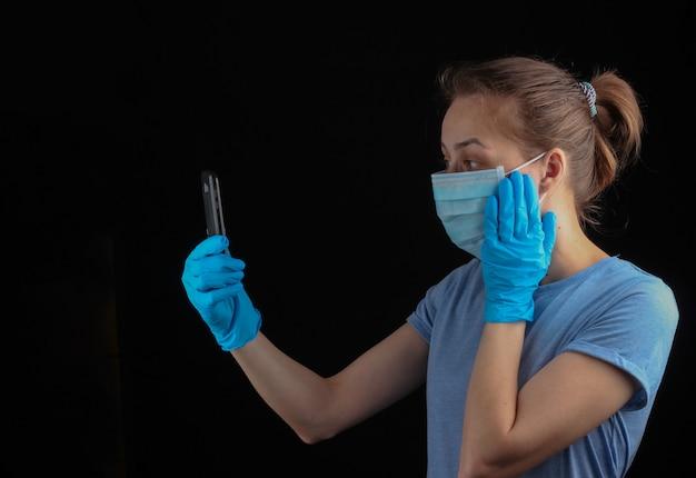 Comunicação durante o período de quarentena. video chamada. uma mulher em luvas médicas e uma máscara facial segura um telefone em uma parede preta.