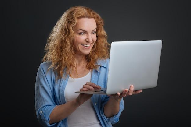 Comunicação eletrônica. uma senhora motivada e fofa inspirada usando seu laptop para se comunicar com seus amigos enquanto fica isolada em um fundo cinza