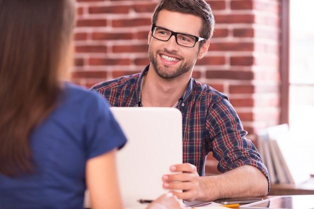Comunicação empresarial. dois executivos em trajes casuais conversando e sorrindo sentados frente a frente à mesa