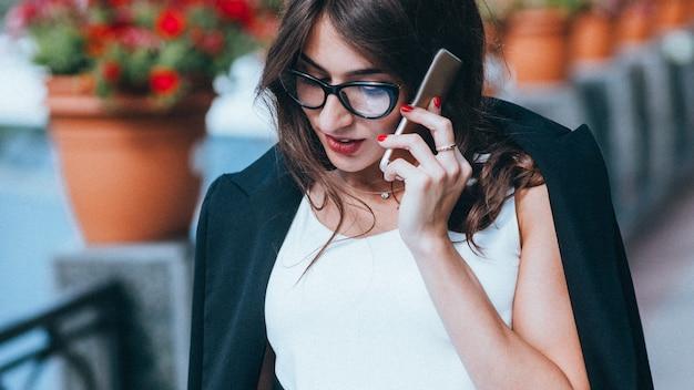 Comunicação empresarial. gerenciamento remoto de projetos. mulher confiante falando no telefone ao ar livre.