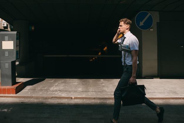 Comunicação empresarial. vida em movimento. homem andando pela cidade fechando negócios ao telefone. sem tempo a perder. estilo de vida agitado