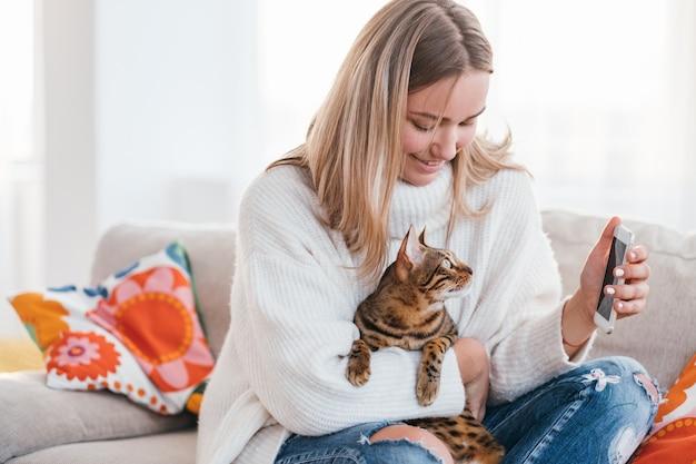 Comunicação entre animais de estimação e proprietários relação humana e animal. garota mostrando uma foto no telefone para o gato dela.