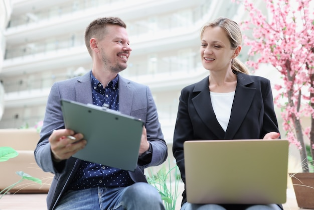Comunicação entre mulher de negócios e empresário e estudo de relatórios da empresa
