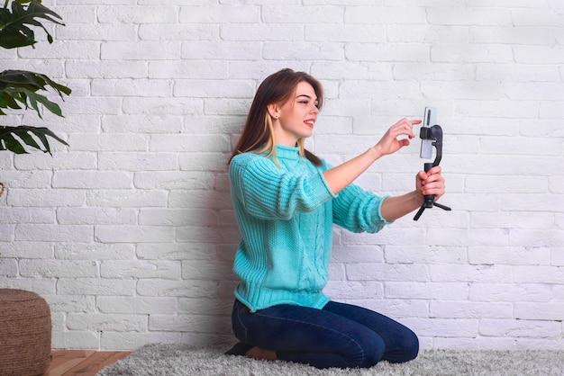 Comunicação fácil e agradável por meio de comunicação de vídeo usando um telefone celular. uma linda jovem cria um blog e se comunica com os seguidores de casa por meio de um link de vídeo