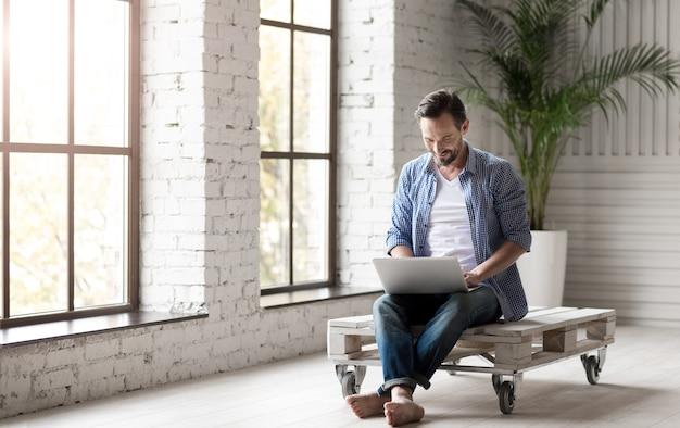 Comunicação interativa. homem simpático e atraente, segurando um laptop e conversando online com alguém enquanto está sentado na sala