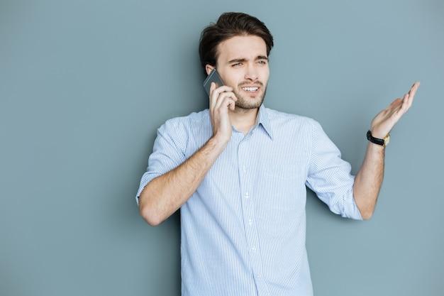 Comunicação não verbal. homem simpático e bonito falando ao telefone e gesticulando enquanto expressa suas emoções