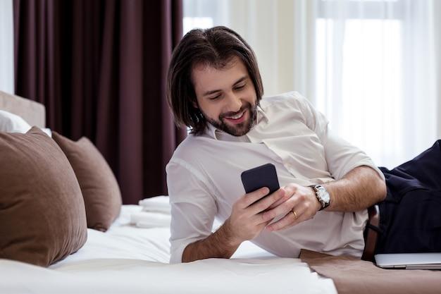 Comunicação online. empresário de sucesso positivo escrevendo uma mensagem enquanto estava deitado na cama em um hotel