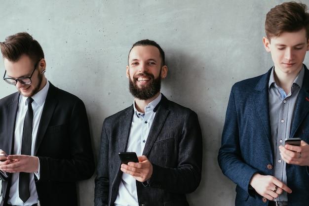 Comunicação online. estilo de vida social moderno. homens de negócios jovens em pé na fila com smartphones.