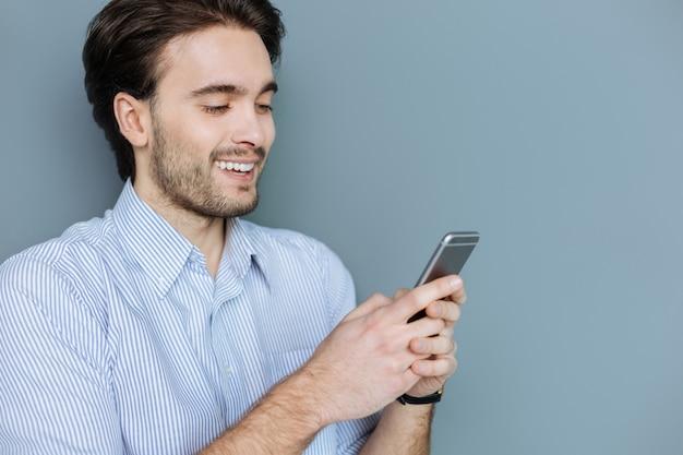 Comunicação online. homem simpático feliz e positivo olhando para a tela e sorrindo enquanto falava com seus amigos online