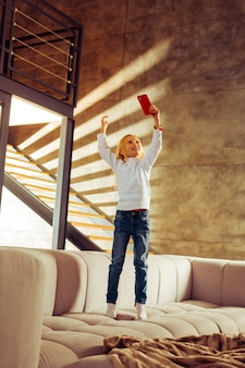 Comunicação online. menina encantadora de pé no sofá segurando o smartphone na mão esquerda