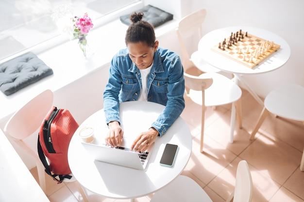 Comunicação online. morena atenta olhando para seu laptop enquanto trabalhava à distância