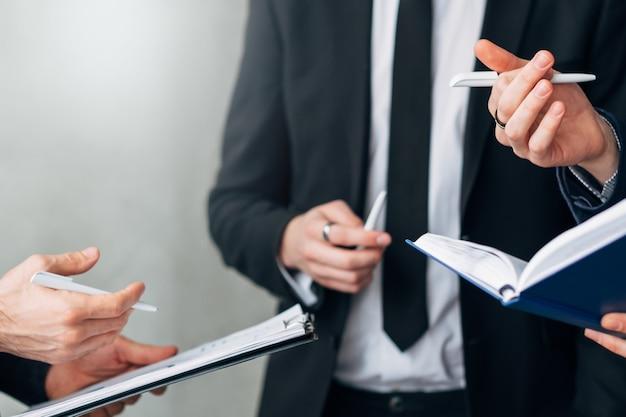 Comunicação profissional. estratégia eficaz. foto recortada de homens de negócios segurando blocos de notas, discutindo ideias.