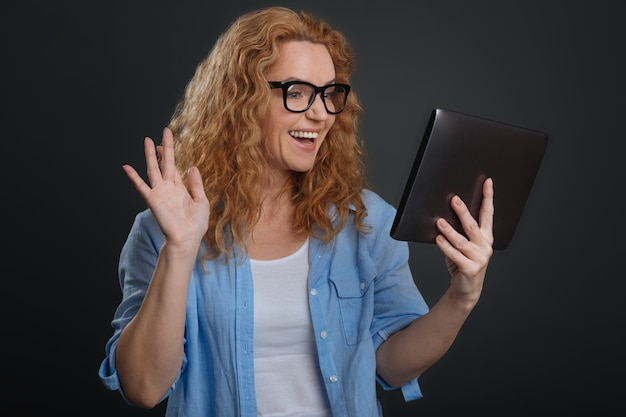 Comunicação sem fronteiras. mulher bonita, amigável e animada, usando tecnologia moderna para estar em contato com conhecidos de todo o mundo e conversar online
