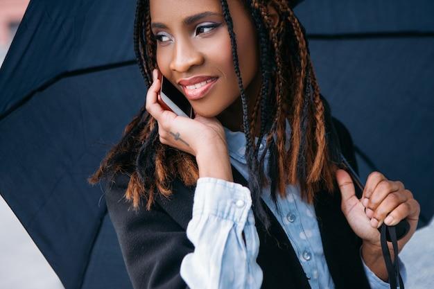 Comunicação social moderna. conversa feliz. clima temperamental, mulher negra alegre com um guarda-chuva em dia chuvoso, conceito de felicidade