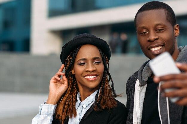Comunicação social moderna. feliz casal negro. elegantes afro-americanos tirando selfie, amigos alegres em foco seletivo, conceito de tecnologia