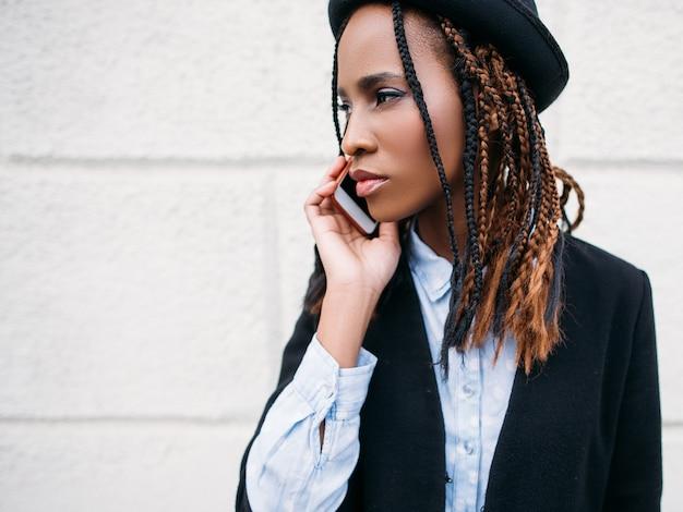 Comunicação social. retrato de menina negra da moda. mulher afro-americana em fundo branco com espaço livre. juventude moderna, conceito de beleza