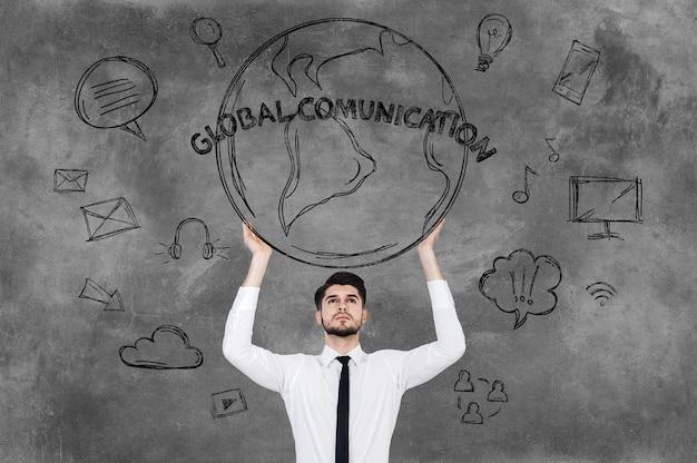 Comunicações globais. jovem bonito com camisa e gravata em pé contra o quadro-negro