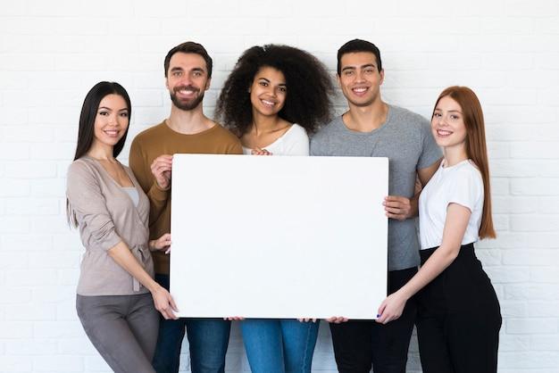 Comunidade de jovens segurando uma placa
