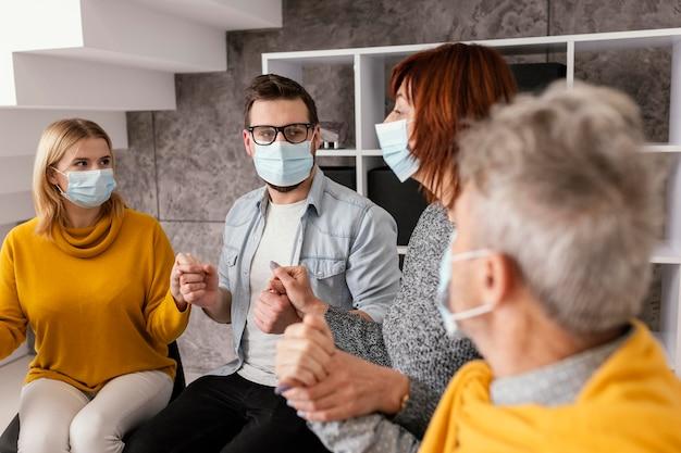 Comunidade de terapia com máscara cirúrgica de mãos dadas Foto Premium