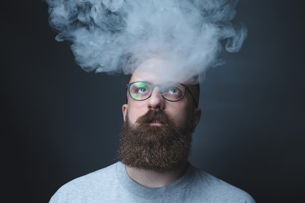 Conceito. a fumaça envolveu o chefe. retrato de um homem barbudo e elegante com fumaça. fumo passivo.
