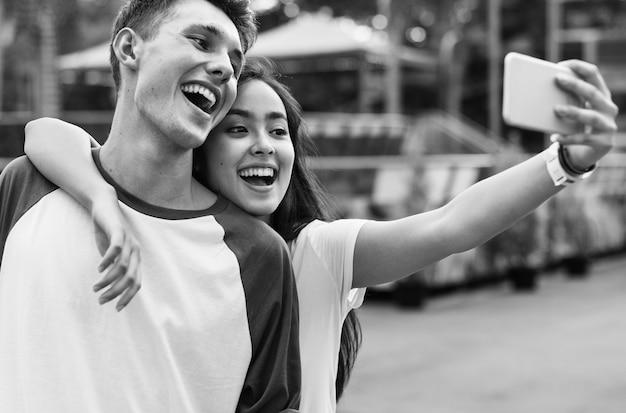 Conceito adolescente de selfie do parque de diversões dos pares