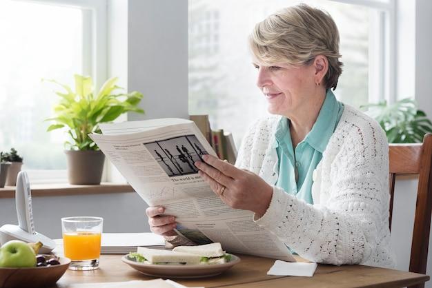 Conceito adulto sênior do lazer do jornal da leitura