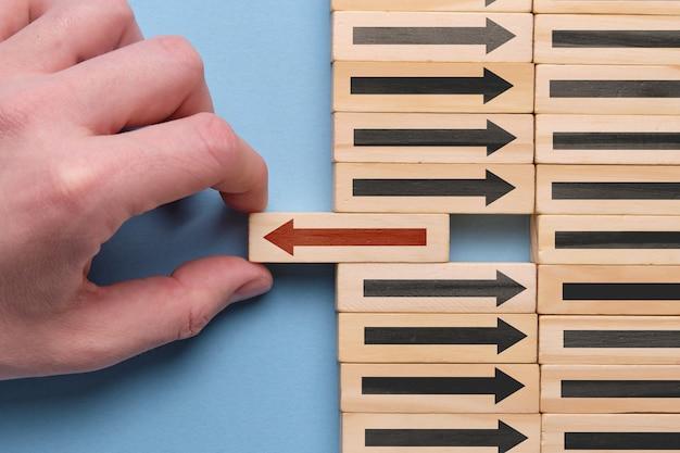 Conceito alternativo do desenvolvimento de negócios - a mão guarda o cubo de madeira com a seta vermelha no espaço azul.