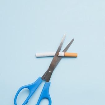 Conceito anti-tabagismo com cigarro e tesoura em pano de fundo colorido