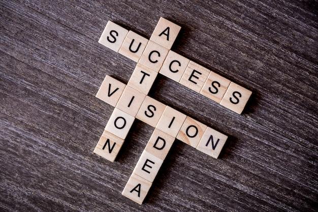 Conceito apresentado por palavras cruzadas com palavras ideia, visão, ação e sucesso com filhote de madeira