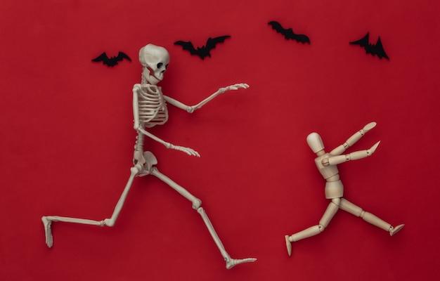 Conceito assustador de halloween. boneco de madeira foge do esqueleto em vermelho com morcegos voadores