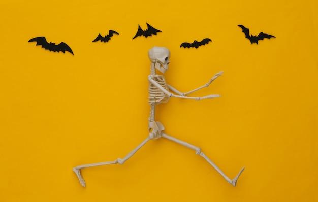 Conceito assustador de halloween. esqueleto foge amarelo com morcegos voadores