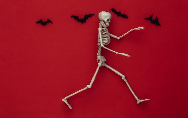 Conceito assustador de halloween. esqueleto foge vermelho com morcegos voadores