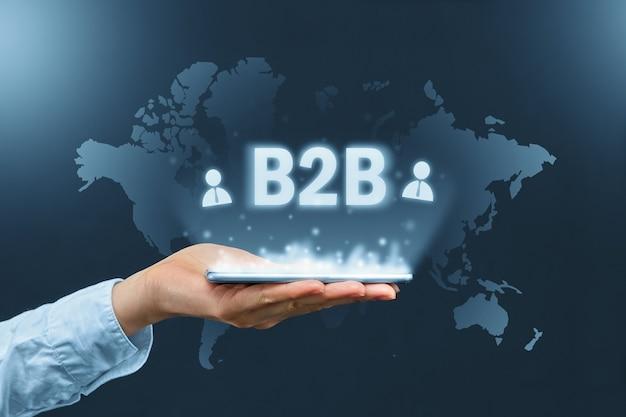 Conceito b2b. inscrição gráfica business to business sobre o smartphone no fundo do mapa-múndi.