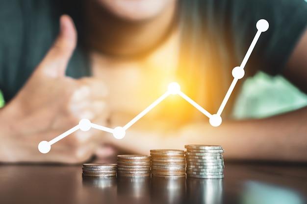 Conceito bem sucedido financeiro do negócio com tendência de alta do gráfico do crescimento do ícone e pilha de dinheiro das moedas de ouro na tabela.
