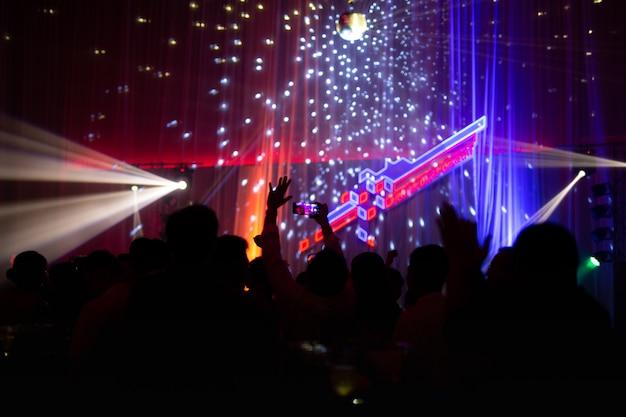 Conceito borrado na festa de concertos com audiência e iluminação conduzida colorida.