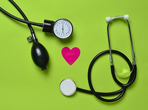 Conceito cardiológico. monômetro médico, estetoscópio, coração decorativo sobre um fundo verde. vista do topo.