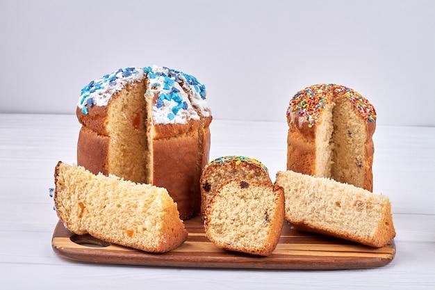Conceito clássico de páscoa eslava. ovos coloridos espumantes e um pedaço de bolo de páscoa saboroso em fundo branco.