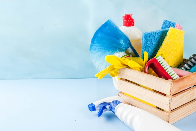 Conceito com suprimentos, pilha de produtos da limpeza da primavera. conceito de tarefa doméstica, na luz azul copyspace