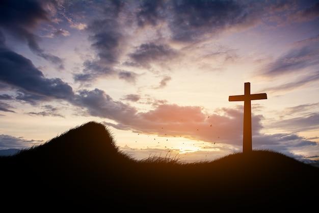 Conceito conceitual da cruz negra silhueta símbolo da religião na grama sobre o céu do pôr do sol