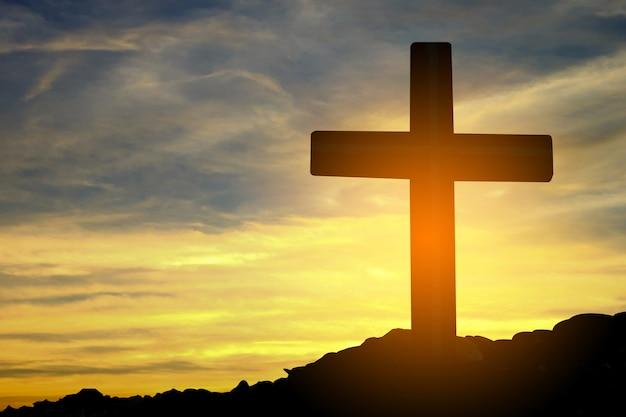 Conceito conceptual religião cruzada símbolo silhueta na natureza ao longo do sol ou céu do nascer do sol