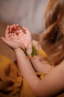 Conceito contra a vacinação, depressão, suicídio, close-up das mãos de uma menina com raminhos de samambaia colados com emplastros nas veias.