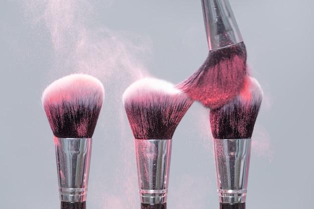 Conceito cosmético de maquiagem, beleza, mineral - pincele com pó rosa sobre fundo claro