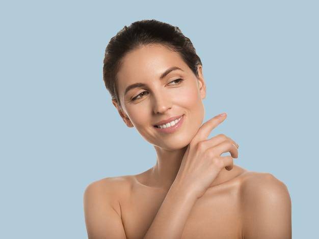 Conceito cosmético de rosto de beleza de pele saudável de mulher bonita tocando seu fundo de cor do rosto. azul.