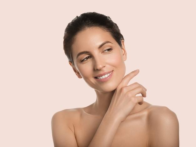 Conceito cosmético de rosto de beleza de pele saudável de mulher bonita tocando seu fundo de cor do rosto. cor de rosa