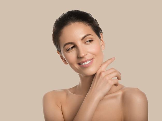 Conceito cosmético de rosto de beleza de pele saudável de mulher bonita tocando seu fundo de cor do rosto. marrom.