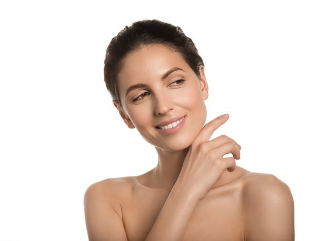 Conceito cosmético de rosto de beleza de pele saudável de mulher bonita tocando seu rosto. isolado no branco