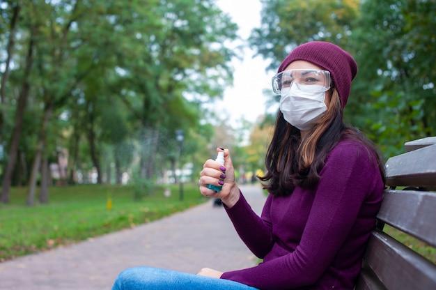 Conceito covid-19. mulher com máscara médica e óculos de proteção, lavando as mãos com álcool gel desinfetante. proteção e prevenção contra coronavírus.